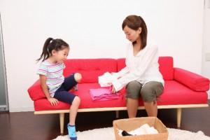 洗濯物をたたむのを手伝おうとしている子供